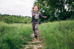 Little boy running down a meadow in a beautiful landscape in summer, very light and happy scene. Curly toddler. Little boy running down a meadow in a beautiful Royalty Free Stock Photos