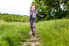 Little boy running down a meadow in a beautiful landscape in summer, very light and happy scene. Curly toddler stock image