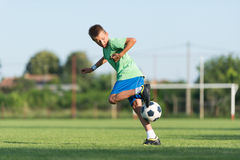 Little boy running dribbling. On the sports field Stock Photography