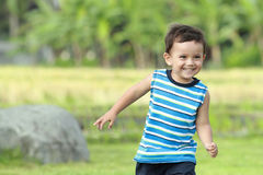 Little boy running on the green nature Stock Image