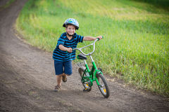 Little boy running with his bike on rural landscape Stock Images