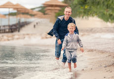 Little boy running with his father at the surf line Royalty Free Stock Photo