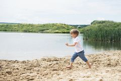 Little Boy Running On A Sand Near A Pond Stock Photos