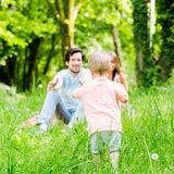 Little boy running over meadow with family in back Royalty Free Stock Photography