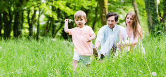 Little boy running over meadow with family in back Stock Photo