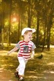Little boy running in the park.1. The little boy runs, has fun in park. Vertical photo Stock Photos
