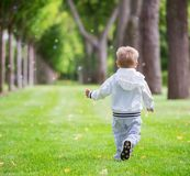 Little boy running in park, rear view. Happy carefree childhood Royalty Free Stock Image