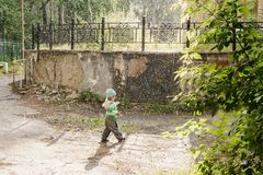 Little boy running in the rain in the Park royalty free stock image