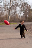 Little boy running with red heart balloon Stock Photography