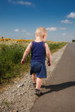 Little boy running on a roadside Royalty Free Stock Images