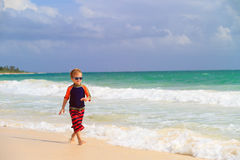 Little boy running on sand tropical beach Stock Photos