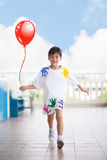 Little boy running at school with happy face taking a red balloon in hand Stock Image