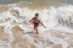 Little boy running in sea surf at the beach Royalty Free Stock Photos