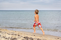 Little boy running at the seashore Royalty Free Stock Image