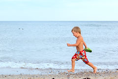 Little boy running at the seashore Royalty Free Stock Photo