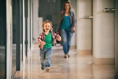 Little boy running in the shopping center with his mom on background. Vintage style Royalty Free Stock Image