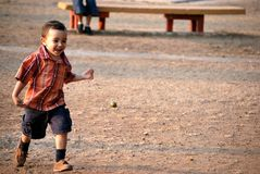 Little boy running and smiling. In the park Stock Photography