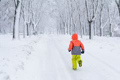 Little boy running on snow. Kid boy running along the road with Royalty Free Stock Photos