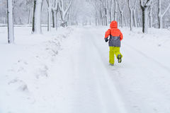 Little boy running on snow. Kid boy running along the road with Royalty Free Stock Photography