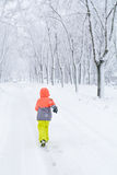 Little boy running on snow. Kid boy running along the road with Stock Photos