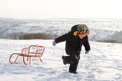 Little boy running through snow with a sled Royalty Free Stock Image