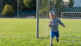 Little boy running on a soccer field Stock Photos
