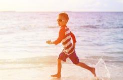 Little boy running splashing water on beach Stock Photos