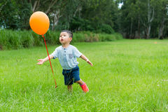 Little boy running to catch with orange balloon Stock Images