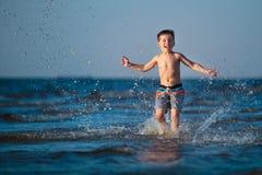 Little boy running through the water at beach Stock Photos