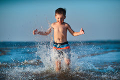 Little boy running through water at the beach Royalty Free Stock Image