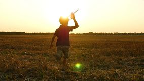 A little boy runs across the field against the sunset, holding a plane in his hand. The child experiences emotions