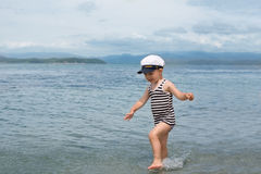 Little boy runs across the sea. Stock Photo