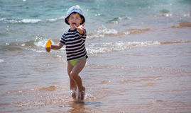 A little boy runs along the seashore and is capricious. A little boy runs along the seashore and is capricious Royalty Free Stock Images