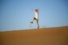 Little boy runs, jumps, plays on top of a sand dune in desert Stock Photo