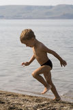 Little boy runs out from water Stock Photos