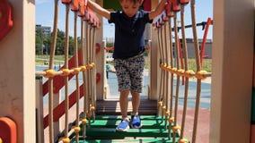 A little boy runs on the playground in the park. Happy child rolls down the children`s slide. Development of preschool stock video
