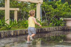 Little boy runs through a puddle. summer outdoor Royalty Free Stock Photography