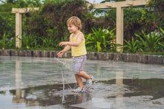 Little boy runs through a puddle. summer outdoor Stock Photo