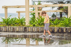Little boy runs through a puddle. summer outdoor royalty free stock images