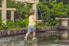 Little boy runs through a puddle. summer outdoor royalty free stock image
