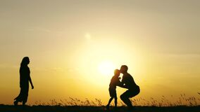 A little boy runs to his father. A happy father throws the child up, playing and kissing it. The concept of a happy