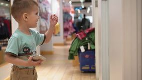 Little boy runs to meet his mom in the store and have fun.  stock footage