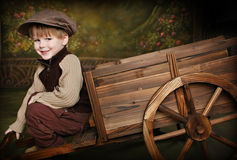 Little Boy with Rustic Wagon. Little Boy dressed in old fashioned garp with Rustic Garden Wagon royalty free stock photo