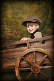 Little Boy in Rustic Wagon. Little Boy dressed in old fashioned garp with Rustic Garden Wagon stock photo