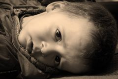Little boy's face. Little boy expressing fatigue. sadness and yet curiosity stock images