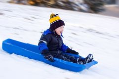 Little Boy's First Sled Ride. Excited Little Boy on First Sled Ride in the Snow Royalty Free Stock Photos