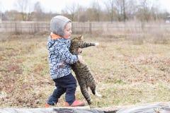 Little Boy s'inquiète d'un chat Images stock