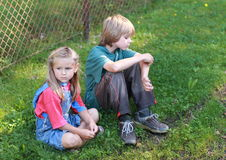 Little boy and sad girl. Sitting in front of a fence Stock Photography