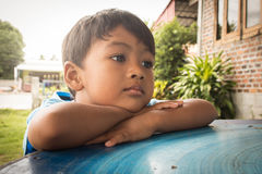 Little boy sad and worried  lying on the table Royalty Free Stock Photos