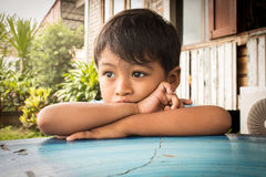 Little boy sad and worried  lying on the table Royalty Free Stock Photo